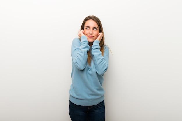 Mulher loura nas orelhas brancas isoladas da coberta do fundo com mãos. expressão frustrada