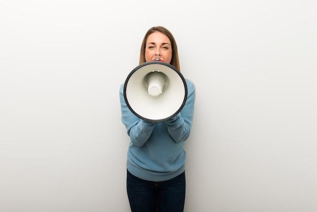 Mulher loura no fundo branco isolado que shouting através de um megafone para anunciar algo