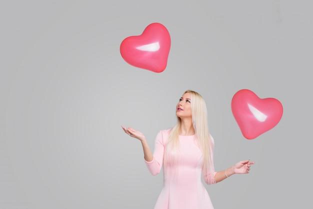 Mulher loura nova bonita com o balão de ar cor-de-rosa da forma do coração no cinza. mulher no dia dos namorados. símbolo do amor - imagem. espaço para texto