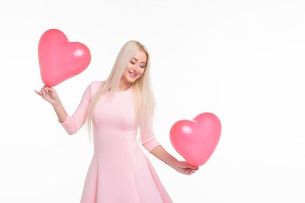 Mulher loura nova bonita com o balão de ar do rosa da forma do coração no branco isolado. mulher no dia dos namorados. símbolo do amor - imagem. espaço para texto