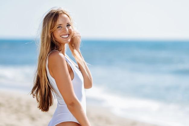 Mulher loura nova com corpo bonito no roupa de banho branco em uma praia tropical.