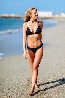 Mulher loura nova com corpo bonito no roupa de banho que anda em uma praia tropical.