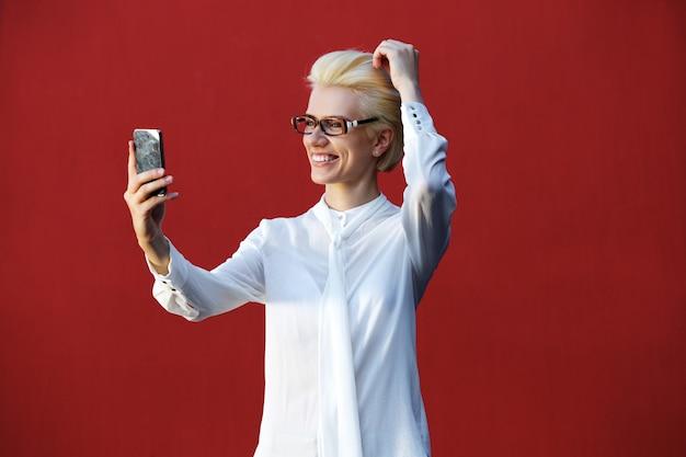 Mulher loura nova de sorriso que toma o selfie