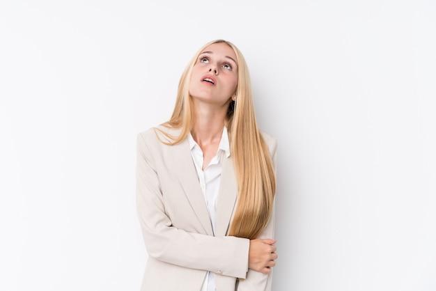 Mulher loura nova do negócio no fundo branco cansado de uma tarefa repetitiva.