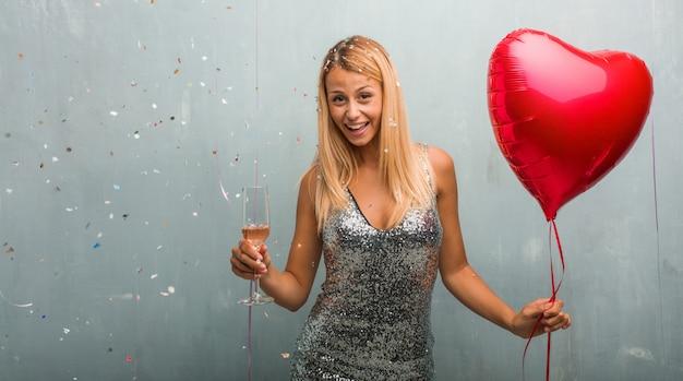 Mulher loura nova elegante que comemora um evento, guardando um copo de champanhe e um balão vermelho do coração.