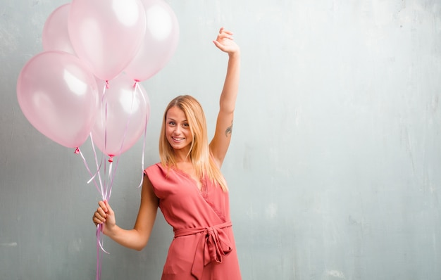 Mulher loura nova elegante que mantém balões cor-de-rosa contra uma parede.