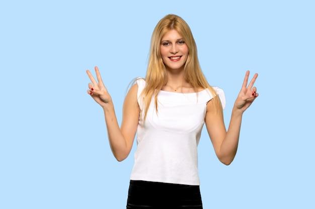 Mulher loura nova que sorri e que mostra o sinal da vitória com ambas as mãos no fundo azul isolado