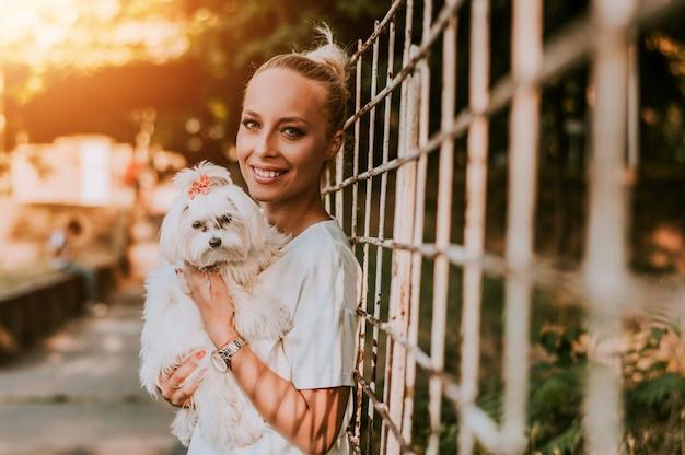 Mulher loura que guarda seu cão maltês.