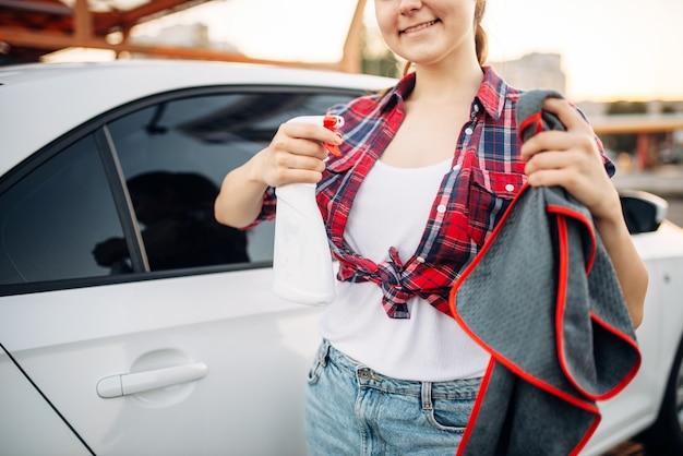Mulher lustra o carro após a lavagem, processo de polimento na lavagem de carro. senhora fazendo limpeza úmida de veículo em lavagem automática de automóveis