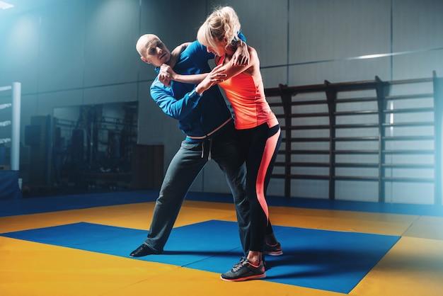 Mulher luta com homem em treinamento de autodefesa, treino de luta na academia, arte marcial
