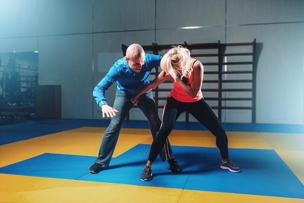 Mulher luta com homem, técnica de defesa pessoal, treino de defesa pessoal com personal trainer na academia, arte marcial