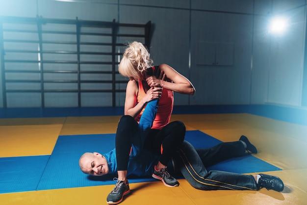Mulher luta com homem, técnica de defesa pessoal, treino de defesa pessoal na academia, arte marcial