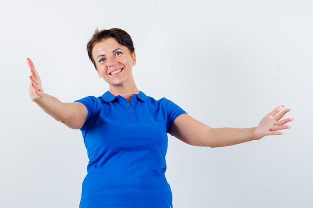 Mulher madura abrindo os braços para um abraço na camiseta azul e olhando feliz. vista frontal.