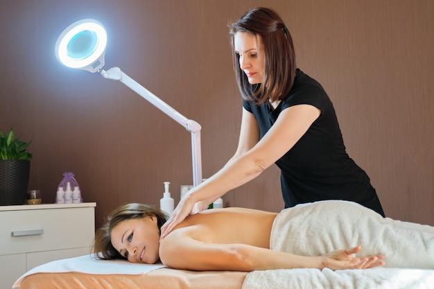Mulher madura adulta, descansando no procedimento de massagem nas costas na mesa de massagem no salão de beleza