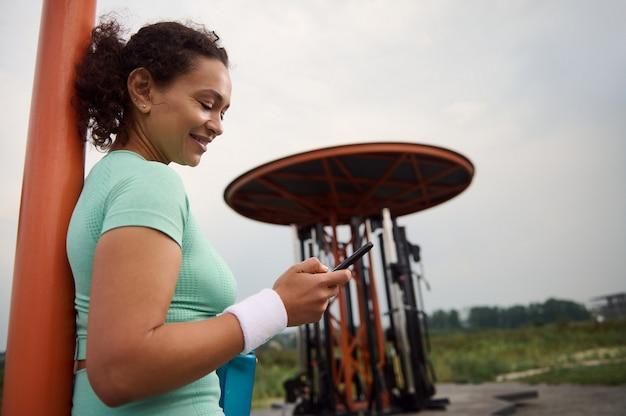 Mulher madura afro-americana de raça mista usando um smartphone, sorrindo, descansando após a sessão de treino, apoiada em uma barra transversal no campo de esportes ao ar livre de verão