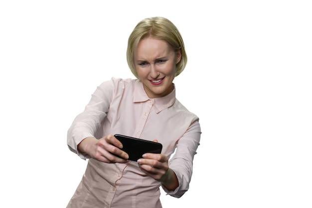 Mulher madura animada jogando videogame em seu smartphone. senhora de meia idade em matar o tempo durante o intervalo do tempo. isolado no branco.