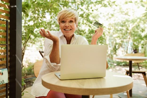 Mulher madura animada, sentado em um café com laptop