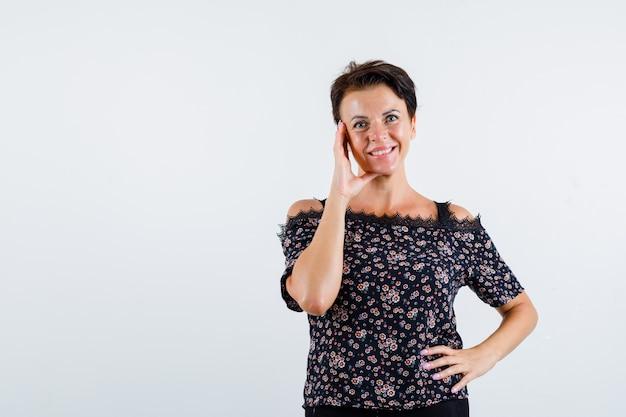 Mulher madura apoiando a bochecha na palma da mão, segurando a mão na cintura em uma blusa floral, saia preta e parecendo confiante, vista frontal.