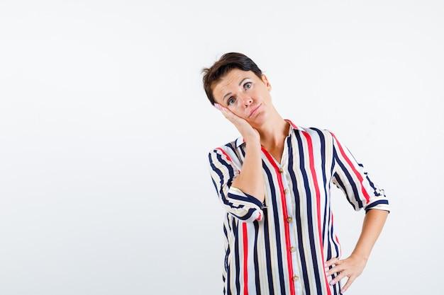 Mulher madura apoiando a bochecha na palma da mão, segurando a mão na cintura em uma blusa listrada e olhando pensativa, vista frontal.
