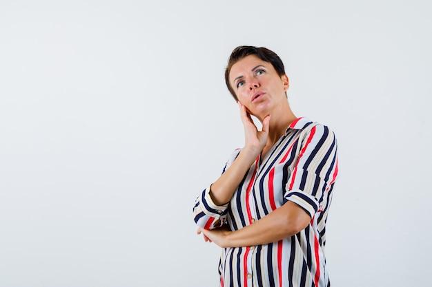Mulher madura apoiando a bochecha na palma da mão, segurando uma mão no cotovelo em uma blusa listrada e olhando pensativa. vista frontal.