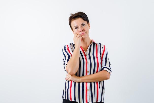 Mulher madura apoiando a bochecha na palma da mão, segurando uma mão sob o cotovelo em uma camisa listrada e olhando pensativa. vista frontal.