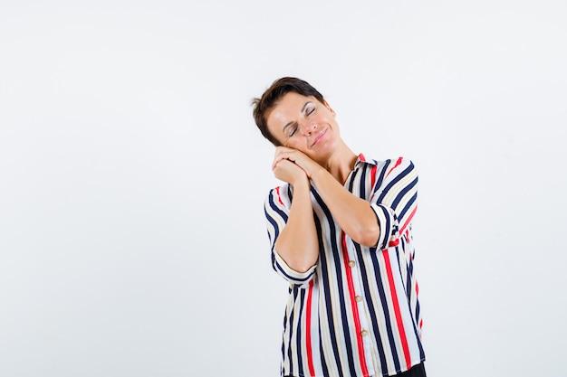 Mulher madura, apoiando a bochecha nas palmas das mãos como travesseiro na camisa listrada e parecendo com sono, vista frontal.