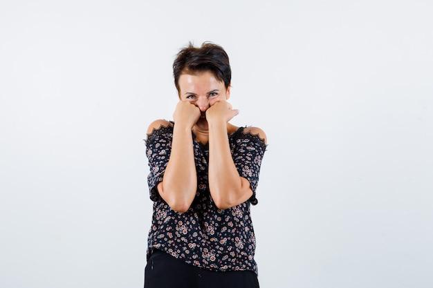 Mulher madura, apoiando os punhos nas bochechas na blusa e olhando bonita, vista frontal.