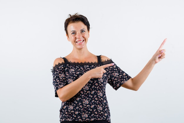 Mulher madura apontando para a direita com o dedo indicador em uma blusa floral, saia preta e parecendo feliz, vista frontal.