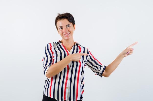 Mulher madura apontando para a direita com o dedo indicador, olhando para cima com a camisa listrada e parecendo feliz, vista frontal.