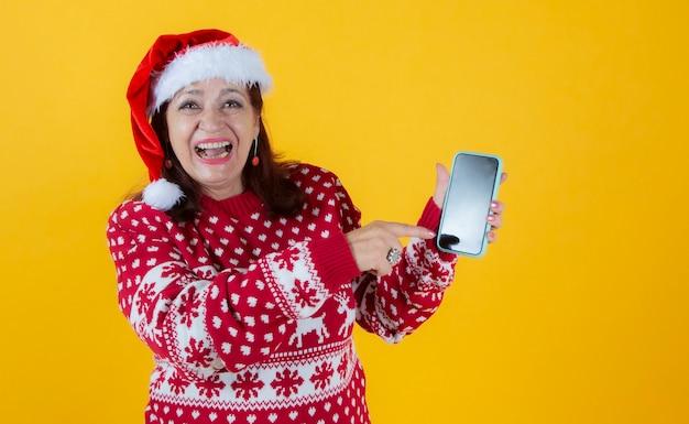 Mulher madura apontando para a tela do smartphone, roupas de natal
