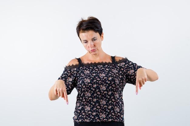 Mulher madura apontando para baixo com o dedo indicador em uma blusa floral, saia preta e olhando séria. vista frontal.