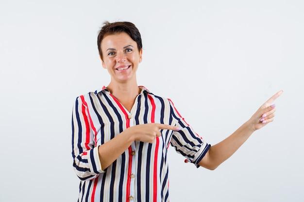 Mulher madura apontando para baixo com o dedo indicador em uma camisa listrada e olhando feliz, vista frontal.