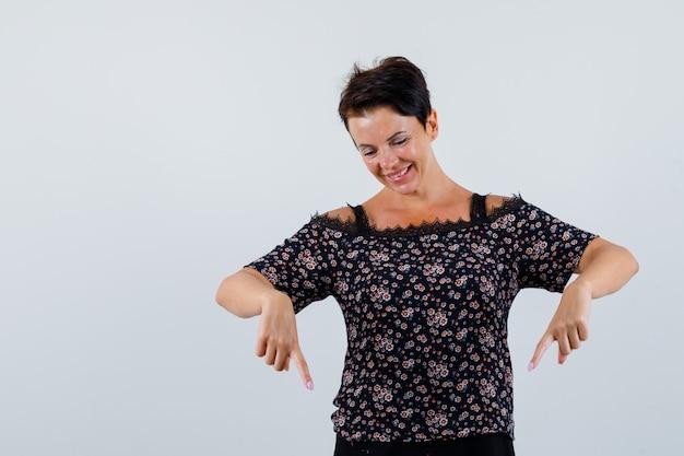 Mulher madura, apontando para baixo na blusa e olhando alegre, vista frontal.
