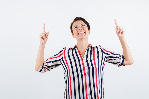 Mulher madura apontando para cima com o dedo indicador, olhando para cima com a camisa listrada e parecendo feliz. vista frontal.