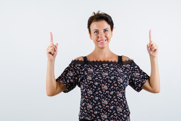 Mulher madura apontando para cima com os dedos indicadores em uma blusa floral, saia preta e parecendo feliz, vista frontal.