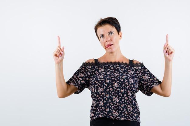 Mulher madura apontando para cima com os dedos indicadores, mostrando a língua em uma blusa floral, saia preta e olhando alegre, vista frontal.