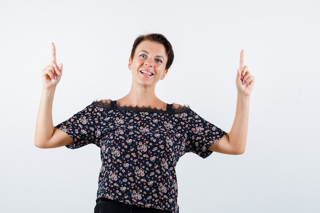 Mulher madura apontando para cima enquanto faz beicinho na blusa e olhando alegre, vista frontal.