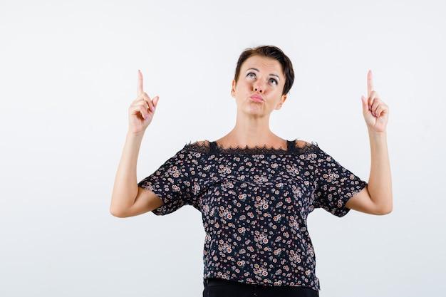 Mulher madura apontando para cima enquanto faz beicinho na blusa e parece pensativa. vista frontal.