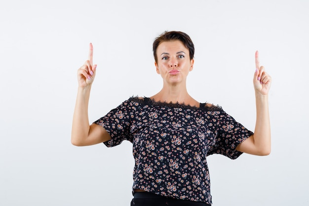 Mulher madura apontando para cima na blusa e parecendo confiante. vista frontal.