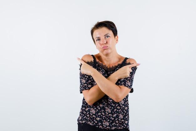 Mulher madura apontando para direções opostas com os dedos indicadores, bochechas infladas em uma blusa floral, saia preta e parecendo séria. vista frontal.