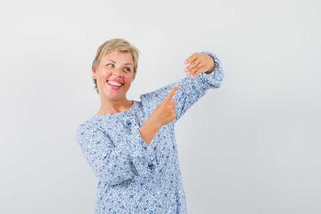 Mulher madura apontando para o anel fingindo estar vestida e parecendo feliz