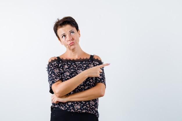 Mulher madura apontando para o lado direito enquanto faz beicinho na blusa e parece pensativa. vista frontal.