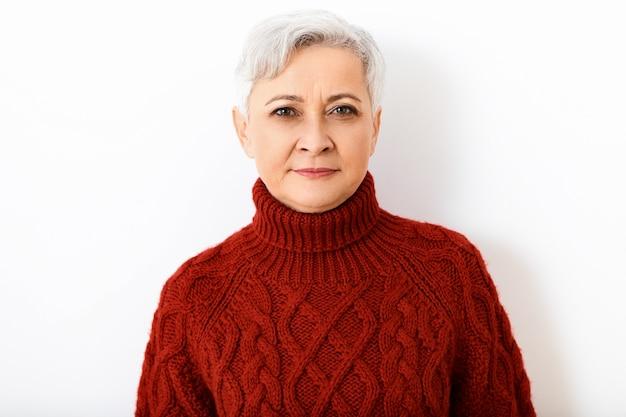 Mulher madura aposentada, séria, de cabelos grisalhos, isolada, usando um suéter de gola alta e uma expressão facial estritamente concentrada ou suspeita, posando contra uma parede branca