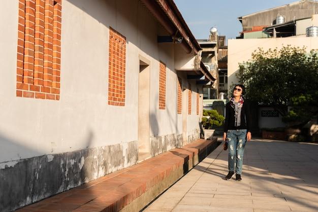 Mulher madura asiática caminhando em um prédio antigo de estilo chinês tradicional