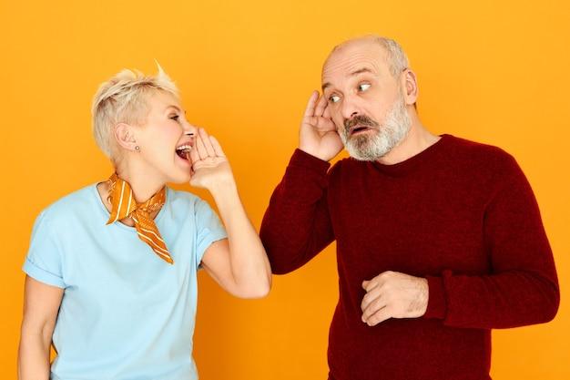 Mulher madura atraente com cabelo curto e grisalho gritando enquanto se dirige ao marido, que está segurando a orelha dele por causa de um problema de audição