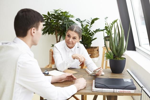 Mulher madura atraente positiva, ceo, conduzindo entrevista de emprego com ambicioso jovem candidato em sua mesa de escritório. pessoas, recursos humanos, recrutamento e emprego