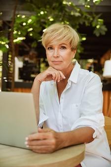 Mulher madura atraente, sentado em um café com laptop