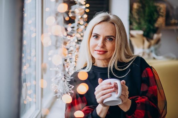 Mulher madura, bebendo café pela janela