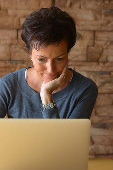 Mulher madura bonita descansando o queixo na mão enquanto usa o laptop na mesa de madeira contra a parede de tijolos