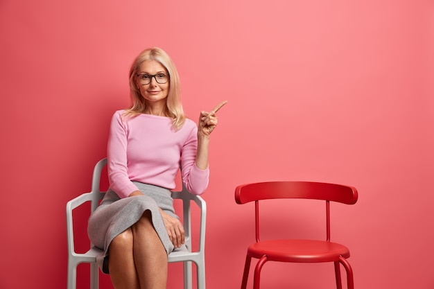 Mulher madura bonita e satisfeita em uma roupa elegante sentada sozinha na cadeira apontando para o espaço da cópia